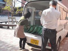 公用車に袋を載せる